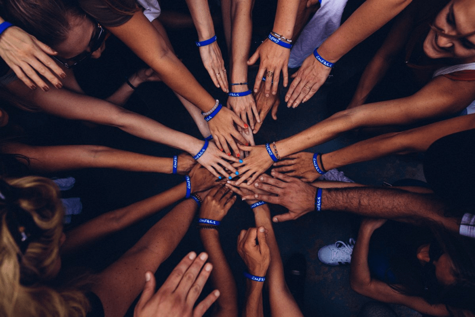 A bird's eye view of a team standing in a huddle, with their arms reached out and their hands meeting in the center, as teams often do before a game. Each team member is wearing a blue bracelet.